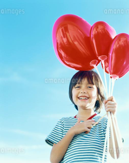 ハートの風船を持つハーフの男の子の写真素材 [FYI04040388]