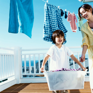 洗濯物を干すハーフの男の子と母の写真素材 [FYI04040398]