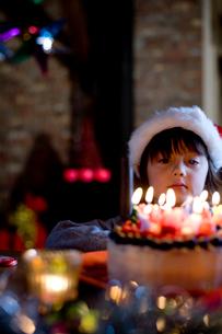 サンタの帽子をかぶったハーフの男の子とケーキの写真素材 [FYI04040529]