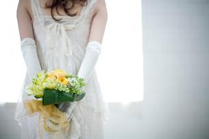 後ろ手にブーケを持つ花嫁の後姿の写真素材 [FYI04040562]