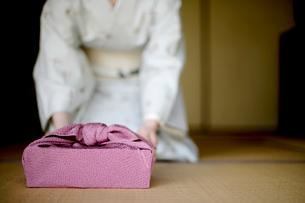 風呂敷包みを差し出す和服の女性の写真素材 [FYI04040627]