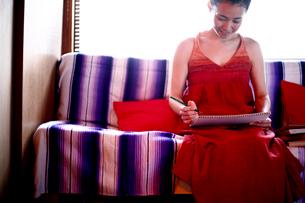 ソファーで絵を描く女性の写真素材 [FYI04040638]