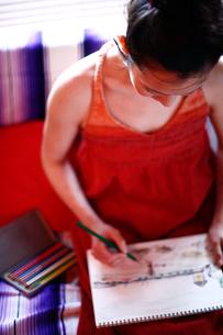 ソファーで絵を描く女性の写真素材 [FYI04040639]