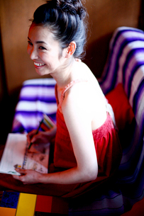 ソファーで絵を描く女性の写真素材 [FYI04040641]