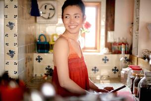 キッチンで料理する女性の写真素材 [FYI04040662]