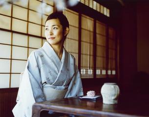 日本茶と和菓子を前にする和服の女性の写真素材 [FYI04040669]