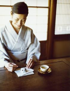 日本茶と和菓子をいただく和服の女性の写真素材 [FYI04040672]