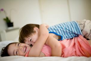 ベッドでくつろぐ男の赤ちゃんと女の子の写真素材 [FYI04040759]