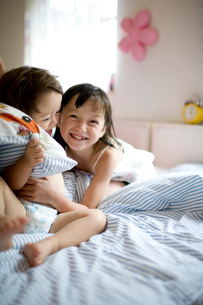 ベッドでくつろぐ男の赤ちゃんと女の子の写真素材 [FYI04040760]