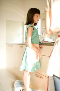キッチンに立つ女の子の写真素材 [FYI04040786]