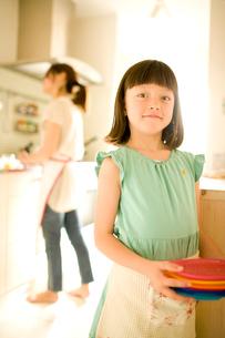 キッチンで皿を持つ女の子の写真素材 [FYI04040800]