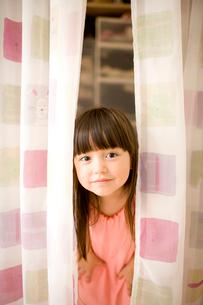 カーテンから顔を出す女の子の写真素材 [FYI04040812]