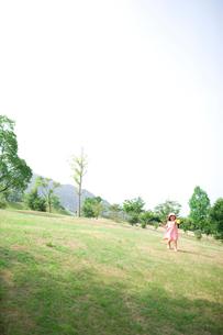 芝生でジョウロを持つ女の子の写真素材 [FYI04040820]