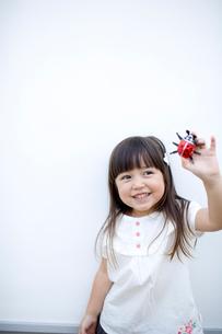 てんとう虫のお菓子を見せる女の子の写真素材 [FYI04040901]