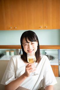 家でワイングラスを片手に笑っている女性の写真素材 [FYI04043032]