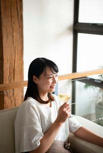 家でワイングラスを片手に笑っている女性の写真素材 [FYI04046397]