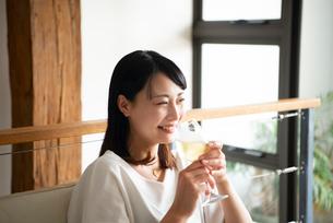 家でワイングラスを持って笑っている女性の写真素材 [FYI04046571]