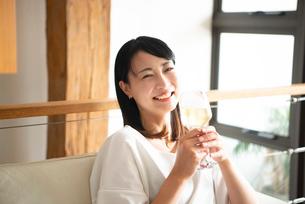 家でワイングラスを持って笑っている女性の写真素材 [FYI04046753]