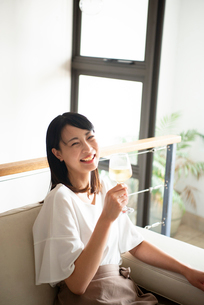 家でワイングラスを持って笑っている女性の写真素材 [FYI04046960]