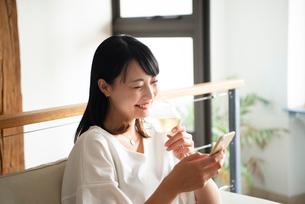 ワイングラスを片手にスマホを見ている女性の写真素材 [FYI04047382]
