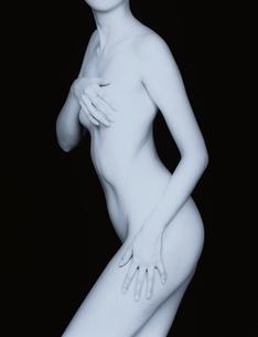 胸を手で隠す女性の横向きのヌード(B&W)の写真素材 [FYI04047710]