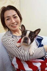 犬(ボストンテリア)を抱っこする日本人中高年女性の写真素材 [FYI04047859]