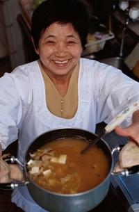 みそ汁が入ったなべを持つ日本人中高年女性の写真素材 [FYI04047861]