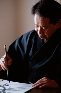 書道を書く日本人老人男性の写真素材 [FYI04047863]