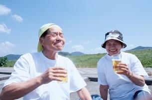 屋外でビールで乾杯する日本人老夫婦の写真素材 [FYI04047868]