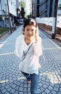 ヘッドホンをして歩く日本人の女の子の写真素材 [FYI04047881]
