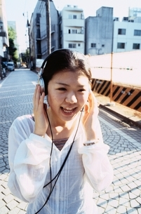 ヘッドホンを聴きながら歩く日本人の女の子の写真素材 [FYI04047883]