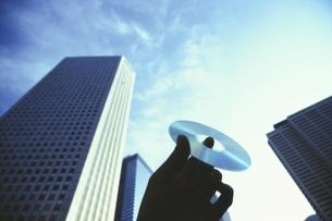 高層ビルとCD-ROMを持つ手 新宿 東京の写真素材 [FYI04047888]