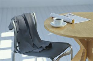 イスに掛けられたジャケットとテーブルの上のコーヒーカップの写真素材 [FYI04047924]