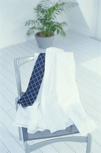 イスに掛けられた白いワイシャツとネクタイの写真素材 [FYI04047927]
