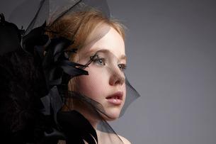 黒い花飾りとブロンド少女の写真素材 [FYI04047966]