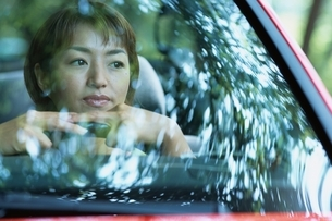 車のハンドルに手を置く日本人女性と木漏れ日の写真素材 [FYI04047981]