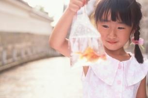 ビニール袋に入った金魚を持った日本人の女の子の写真素材 [FYI04048828]