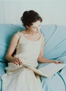 ソファで本を読む外国人女性の写真素材 [FYI04048873]