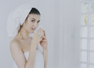 窓際で飲み物を飲むバスタオル姿の外国人女性の写真素材 [FYI04048893]