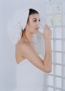 窓際で飲み物を飲むバスタオル姿の外国人女性の写真素材 [FYI04048894]