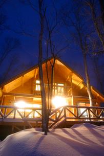 積雪と明かりの灯るログハウスの写真素材 [FYI04049926]
