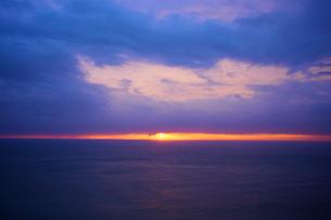 雲間から見える夕日と夕方の海の写真素材 [FYI04050029]