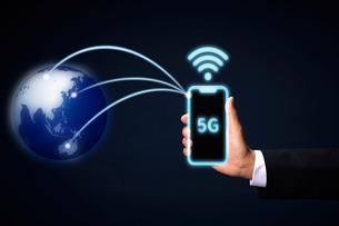 地球へ光の曲線を放つスマートフォンを持つ男性の手と5Gの文字の写真素材 [FYI04051292]