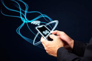 5Gの文字が書かれたスマートフォンを持つ男性の手と光線の写真素材 [FYI04051314]