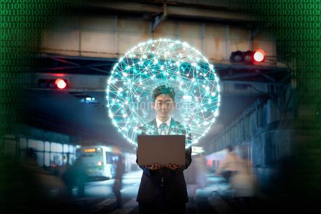 街中でパソコンを開く男性と丸く描かれた点と線のCGの写真素材 [FYI04051460]