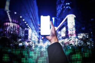 ブロック状になった夜の街の背景とスマートフォンを持つ手の写真素材 [FYI04051482]
