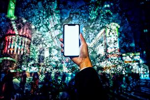 ブロック状になった夜の街の背景とスマートフォンを持つ手の写真素材 [FYI04051520]