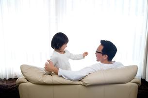ソファーに座る父親と娘の写真素材 [FYI04051640]