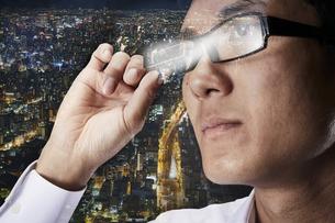 スマートグラスをかける男性と都会の夜景の背景の写真素材 [FYI04051746]