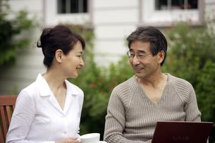 庭でくつろぐ熟年の夫婦の写真素材 [FYI04051799]